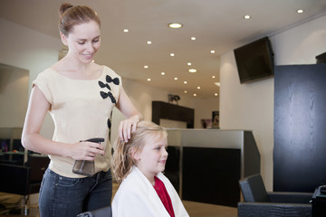 A female hairdresser spraying water on a young girls hair