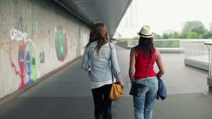 Female friends walking in the city, steadicam shot