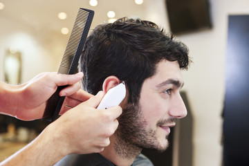 A male hairdresser cutting his male clients hair with a shaver