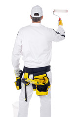 construction worker in white overalls with paint roller paint th