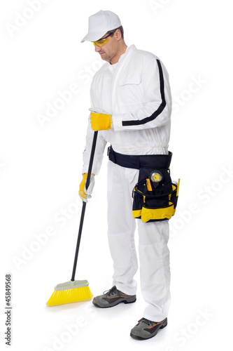construction worker in white overalls sweeping with a broom on w