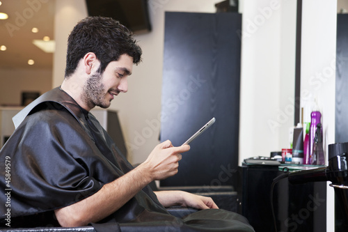 A male client looking at a digital tablet in a hairdressers