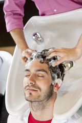 A male hairdresser shampooing a male clients hair