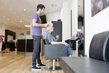 A male hairdresser discussing a female clients hair