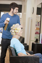 A male hairdresser applying hairspray to a female clients hair