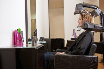 Woman looking at herself in a mirror in a hairdressing salon
