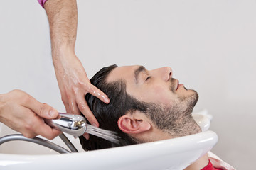 A male hairdresser washing a male clients hair, close up