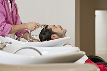 A male hairdresser washing a male clients hair