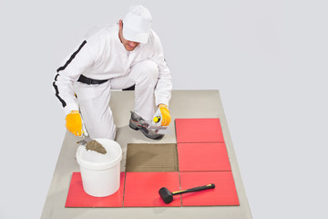 Worker Applies with noched trowel Red Tile on a Floor