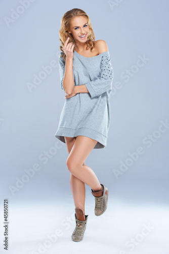 Cute woman wearing long shirt while posing against a gray