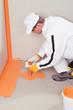 worker brush applied waterproofing on the floor of the bathroom