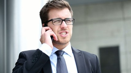Outdoor portrait of a businessman speaking at the phone