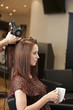 A male hairdresser blow drying a female clients hair