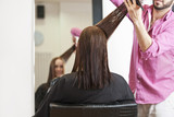 A male hairdresser cutting his female clients long hair