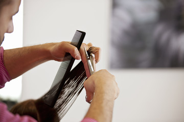 Male hairdresser cutting female client's long hair, close up