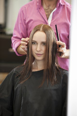 A male hairdresser cutting his female client's long hair