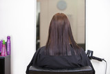 A female client at mirror in a hairdressing salon, rear view