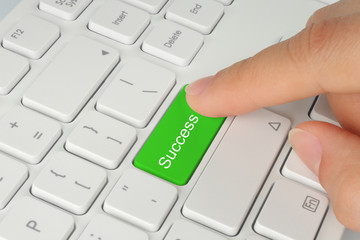 Hand pushing green success keyboard button