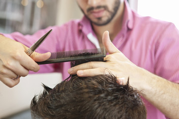 A hairdresser cutting man's hair with scissors, close up