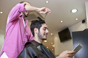 Man looking at a digital tablet whilst having his hair cut