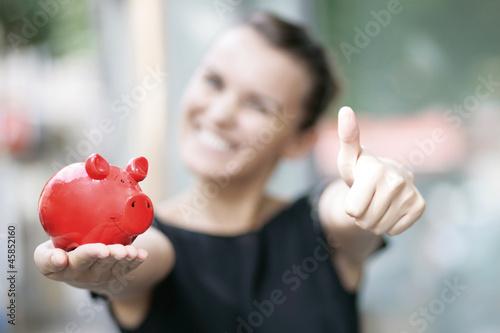 zufriedene Frau mit Sparschwein