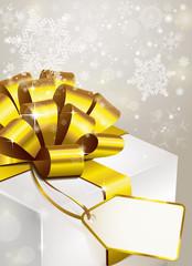 weihnachtsgeschenk mit goldener Schleife u. Label