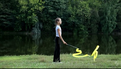 Девушка проводит тренировку на природе с гимнастической лентой