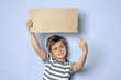 Kind mit Pappschild mit Textfreiraum