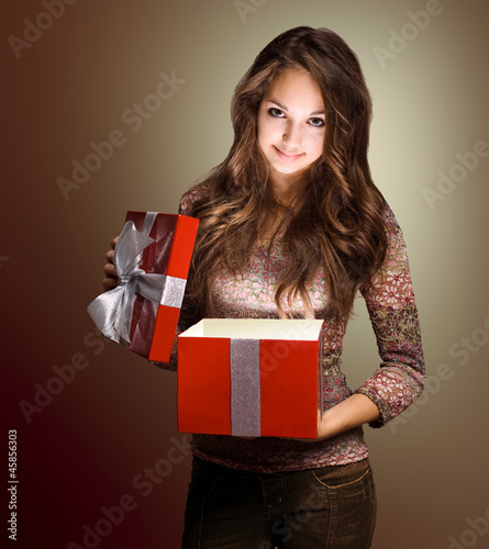Beautiful brunette peeking inside gift box.