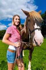 Junge Frau reitet auf dem Pferd auf der Wiese