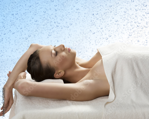 pretty girl lying on a table with towel with arms behind the hea