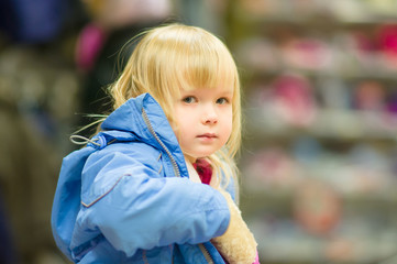 Adorable girl sit on shopping cart and selecting clothes