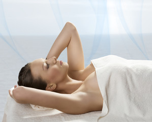pretty girl lying on a table with towel with hands near the head
