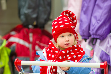 Adorable baby on cart choose clothes in supermarket. Try on red