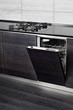 Open dish washer machine and gas-stove on black hardwood kitchen