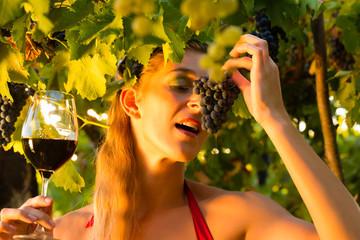 Frau mit Wein Glas isst Weintrauben
