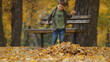 Seven year old boy throws autumn leaves and running