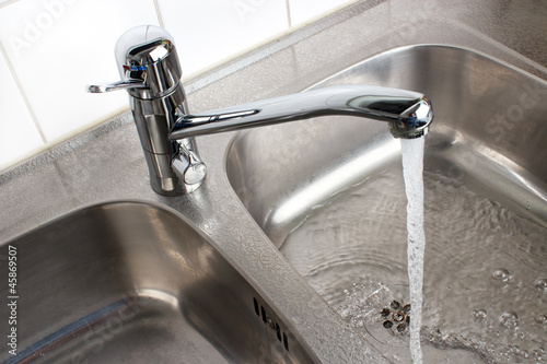 Water flowing from the faucet to  washbasin