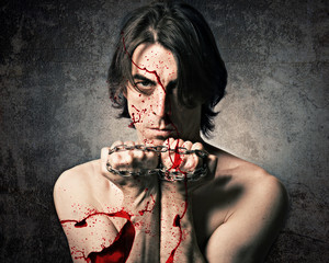 Terrible evil man with an iron chain and covered in blood.