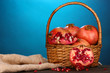 Ripe pomegranates on basket on wooden table on blue background