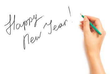 Woman's hand with a pencil writing Happy New Year