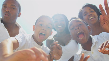 Close up of ethnic  family waving to camera on beach