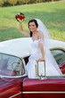 Wedding, bride on vintage car wave with bouquet