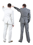 Back view of two businessman pointing at wall. rear view.