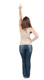 Back view of young brunette woman pointing at wall . beautiful g