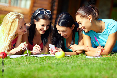 group of happy college girls chatting in network on green lawn