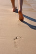 Details of legs of young woman walking through sand in the beach