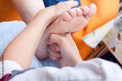 Pflegerin massiert Fuss einer Patientin