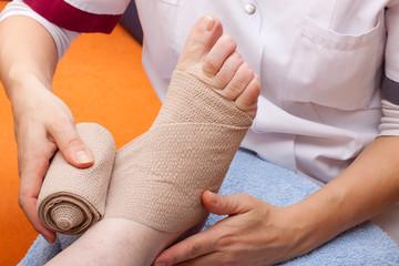 Ärztin bandagiert fuss einer Patientin