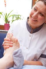 Pflegerin wäscht den fuss einer Patientin
